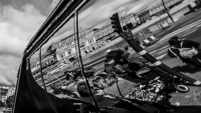 Busfenster, in dem sich Menschen spiegeln